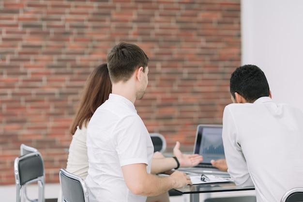 Zespół biznesowy analizujący statystyki danych finansowych na laptopie .koncepcja biznesowa