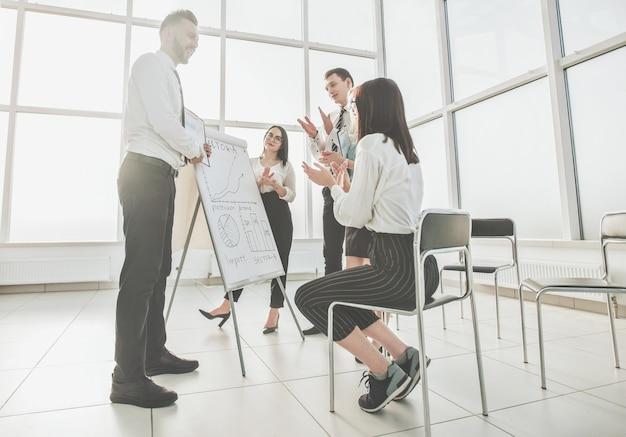 Zespół biznesowy bije brawo prelegentowi podczas prezentacji biznesowej