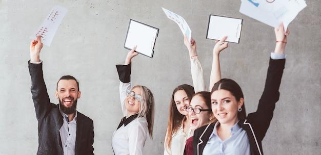 Zespół biznesowy. dział sprzedaży świętujący sukces firmy. podekscytowany uśmiechnięty mężczyzna i kobieta z rękami i papierami w powietrzu