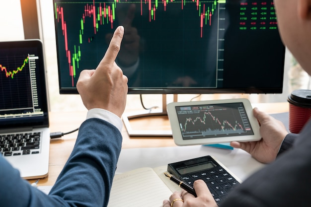 Zespół biznesowy inwestor przedsiębiorca handel omawianie i analiza danych na wykresach giełdowych.