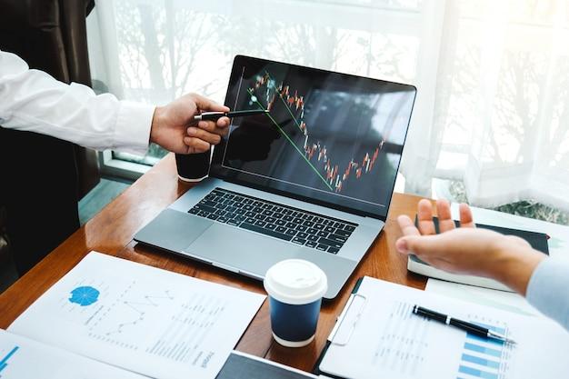 Zespół biznesowy inwestycja przedsiębiorca trading omawianie i analiza wykresu obrotu giełdowego