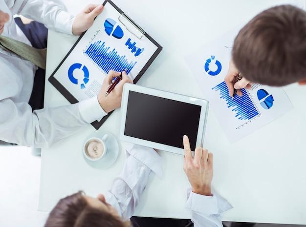 Zespół biznesowy korzystający z cyfrowego tabletu, pracujący z harmonogramem finansowym rozwoju firmy