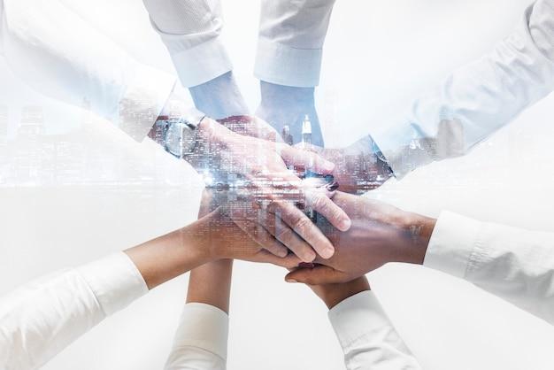 Zespół biznesowy łączący ręce razem w tle miasta