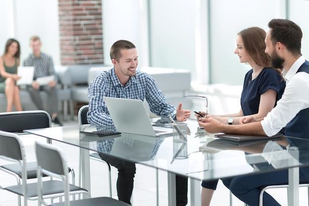 Zespół biznesowy, omawiając nowe pomysły, siedząc przy biurku