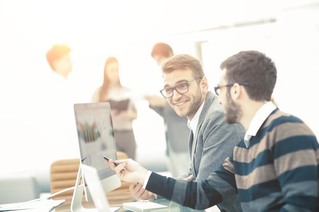 Zespół biznesowy omawiający schematy marketingowe w miejscu pracy na tle pracowników firmy. zdjęcie ma puste miejsce na twój tekst.