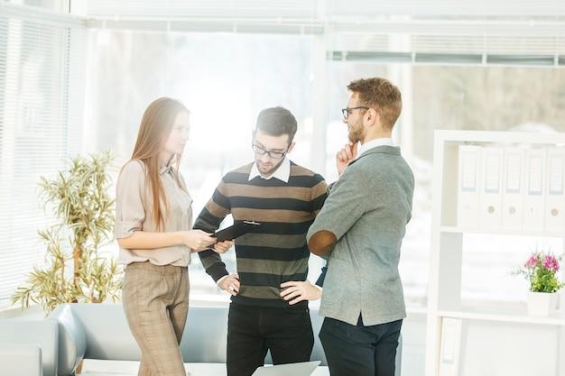 Zespół biznesowy omawiający schematy marketingowe w miejscu pracy na tle pracowników firmy