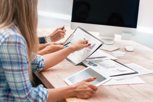 Zespół biznesowy omawiający sprawozdanie finansowe siedząc przy biurku. uruchomienie