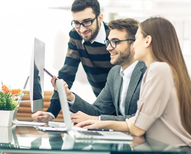 Zespół biznesowy opracowuje nowy projekt, siedząc za biurkiem