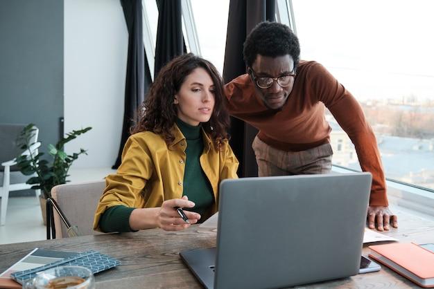 Zespół biznesowy patrzący na monitor komputera i omawiający wspólną pracę online podczas spotkania w biurze