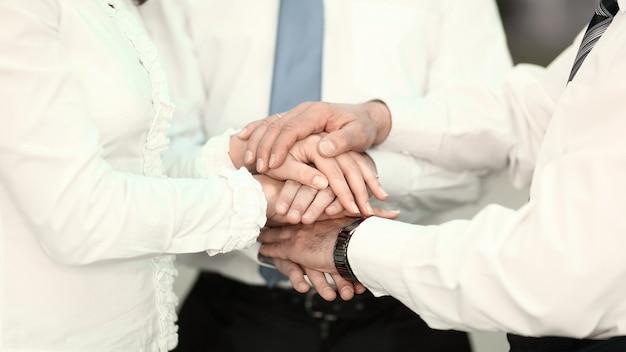 Zespół biznesowy pokazuje swoją jedność splecione razem. koncepcja pracy zespołowej