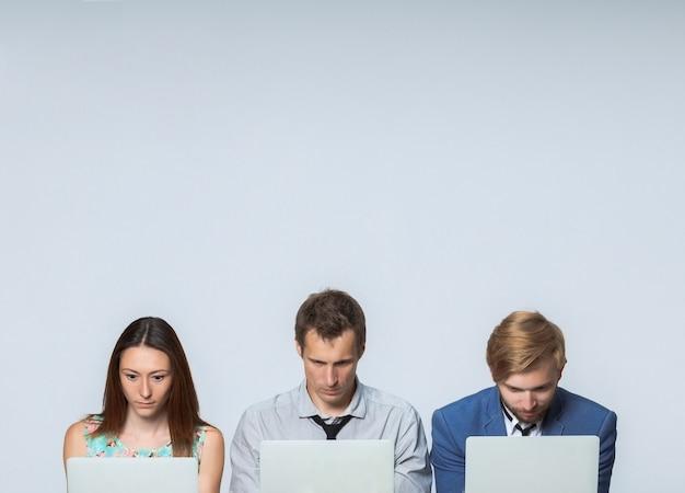 Zespół biznesowy pracujący na laptopach w biurze na szarym tle