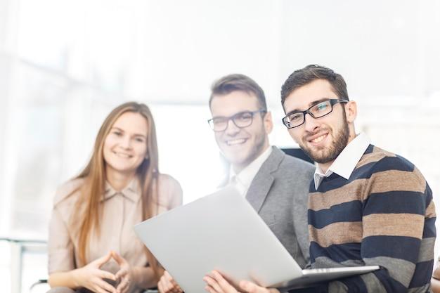 Zespół biznesowy pracujący na laptopie i omawiający sprawy biznesowe.