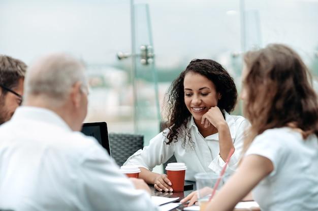 Zespół biznesowy siedzi przy stole dyskusyjnym w centrum biznesowym