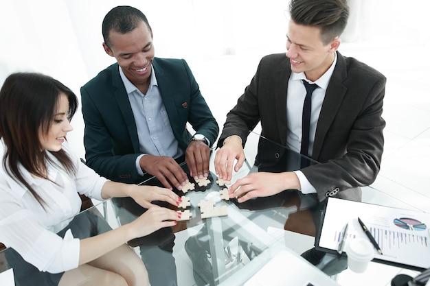 Zespół biznesowy, składając kawałki układanki, siedząc za biurkiem