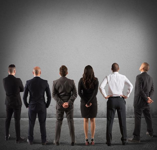 Zespół biznesowy spojrzeć na szarą pustą ścianę