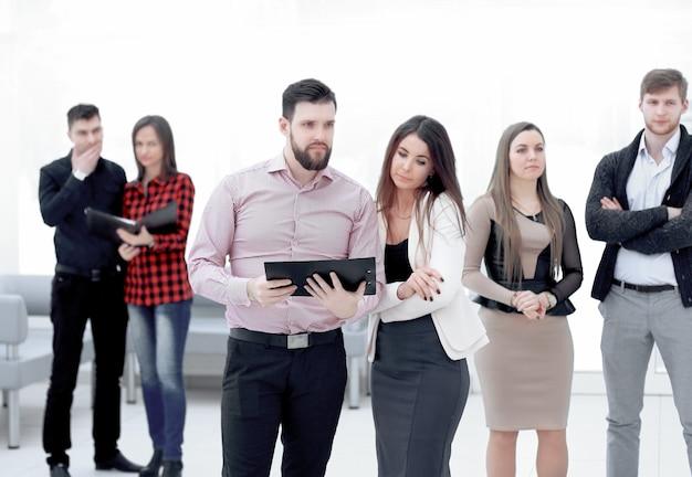 Zespół biznesowy stojący w biurze przed rozpoczęciem spotkania roboczego