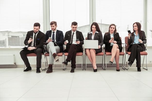 Zespół biznesowy szukający informacji w internecie za pomocą smartfona i laptopa siedząc w holu nowoczesnego biura