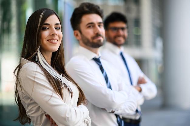 Zespół biznesowy uśmiechający się na zewnątrz w nowoczesnej, miejskiej scenerii