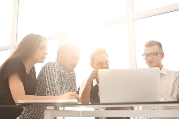 Zespół biznesowy używa laptopa do pracy z dokumentami. pojęcie pracy zespołowej