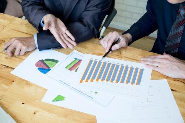 Zespół biznesowych omawianie ich pomysły w biurze. współpraca ze sobą współpracuje. analiza wykresu