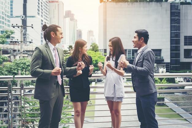 Zespół biznesowych podnosząc ręce i świętując zwycięstwo przed biurem