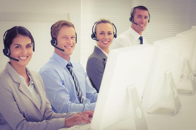 Zespół biznesowych pracujących na komputerach i noszenie zestawów słuchawkowych