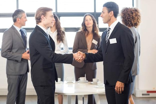 Zespół biznesu stały razem i interakcji w biurze