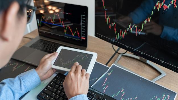 Zespół brokerów lub handlowców rozmawiających o rynku forex na wielu ekranach komputerów giełdy