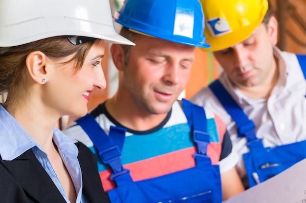 Zespół budowy lub architekt i konstruktor lub pracownik w kaskach kontrolujący lub prowadzący dyskusję na temat planu lub planu