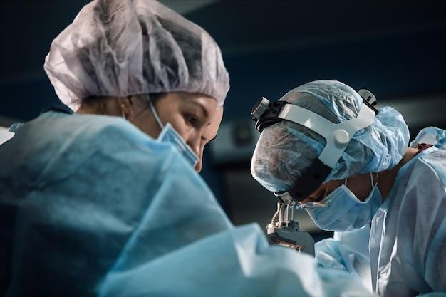 Zespół chirurgiczny na sali operacyjnej, zbliżenie. międzynarodowy zespół profesjonalnych lekarzy w nowoczesnej sali operacyjnej przechodzi operację
