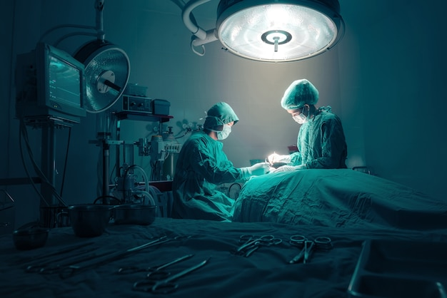 Zespół chirurgów pracujących z monitorowaniem pacjenta w sali operacyjnej.