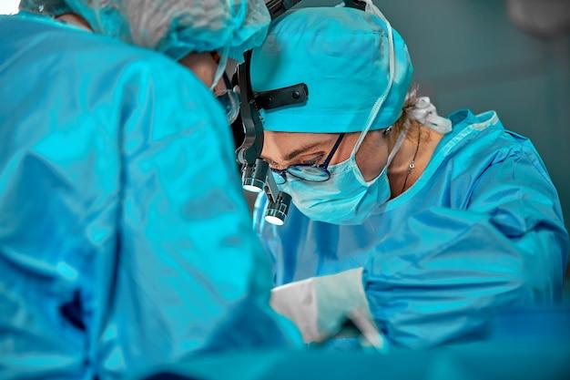 Zespół chirurgów w sali operacyjnej, portrety z bliska. nowoczesna operacyjna chirurgia plastyczna. przemysł kosmetyczny