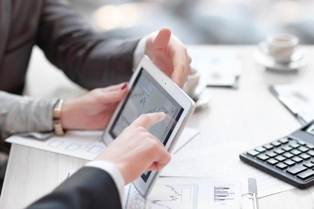 Zespół close up.business omawiający wykresy finansowe za pomocą cyfrowego tabletu.ludzie i technologia