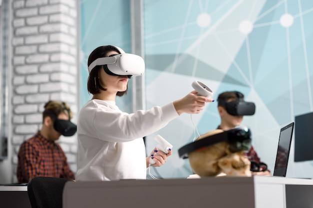 Zespół czterech kreatywnych inżynierów pracujących z wirtualną rzeczywistością, młoda kobieta testująca okulary lub gogle vr siedząca w biurze
