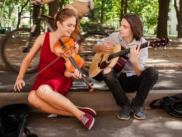 Zespół duetu muzyki ulicznej występujący w parku. koncepcja romansu hipisowskiego wolnych duchów