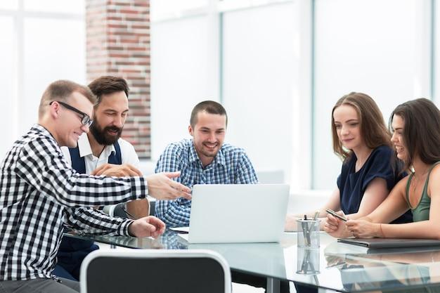 Zespół firmy patrząc na ekran laptopa i omawiając swoje pomysły. ludzie i technologia