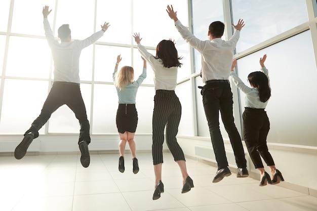 Zespół firmy rear view.happy, bawi się w jasnym nowym biurze. koncepcja startupu