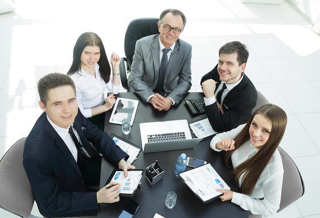 Zespół firmy siedzi przy biurku i patrząc na kamery