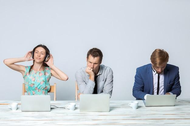 Zespół firmy współpracuje w biurze na jasnoszarym tle. wszystko działa na laptopach. dziewczyna w słuchawkach słuchania muzyki
