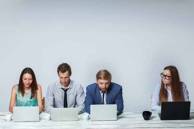 Zespół firmy współpracuje w biurze na jasnoszarym tle. wszystko działa na laptopach. obraz copyspace