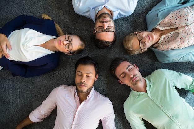 Zespół firmy z zamkniętymi oczami, leżąc na podłodze z głową razem