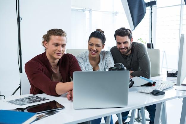 Zespół fotografów pracujących nad laptopem przy biurku