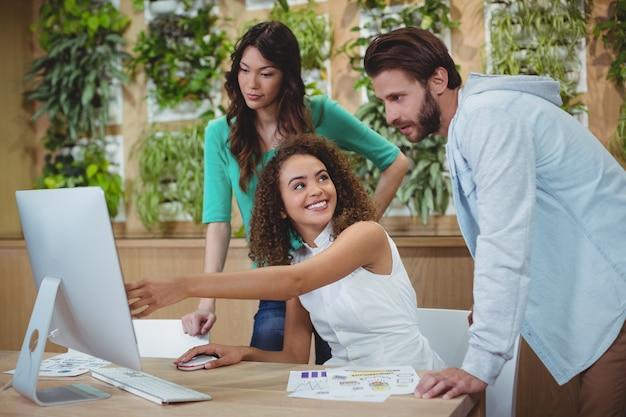 Zespół grafików dyskutujących przy komputerze przy biurku