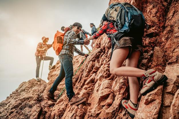 Zespół group hiker pomagający jej przyjaciółce wspiąć się na ostatni odcinek zachodu słońca w górach