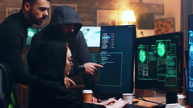 Zespół hakerów patrzący na komputer z wieloma monitorami podczas popełniania cyberprzestępstw.
