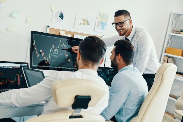 Zespół innowatorów. grupa młodych, nowoczesnych mężczyzn w strojach formalnych, pracujących przy komputerach, siedząc w biurze