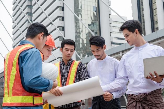 Zespół inżyniera z biznesmenem z myanmaru organizuje spotkanie projektowe i omawia projekt budowlany w mieście at