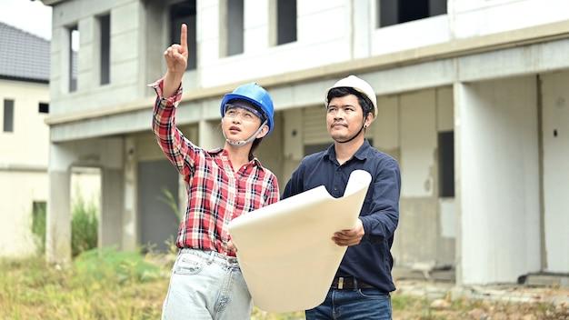 Zespół inżynierów dyskutuje i pracuje na placu budowy. inspekcja przy projekcie wsi i budowie osiedla.