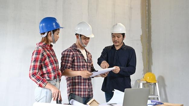 Zespół inżynierów dyskutuje i pracuje na placu budowy. inspekcja właścicielska przy projekcie wsi i budynku osiedla.