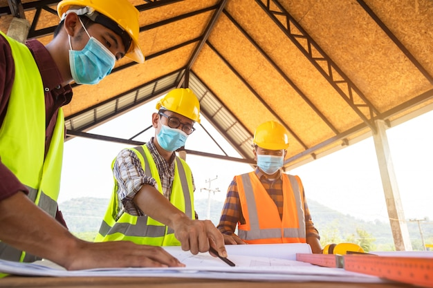Zespół inżynierów i architektów pracujących, spotykających się, jest gotowy do noszenia masek medycznych